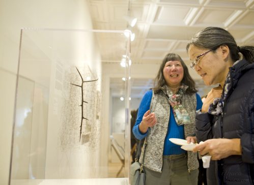 Joe McIntyre/photographer - Elaine Kuo, right, and friend Alice Wu of Ithaca view Jayoung Yoon's sculpture, Jayoung Yoon's 'Sensing Thought 05' (Glue and thorn fragment wrapped with Artist's hair) during the opening reception of 'Intricate Universe' at Corner's Gallery opening reception in Cayuga Heights. 2019